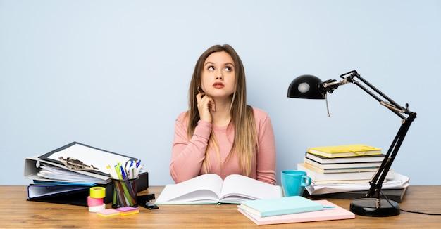 Menina adolescente estudante no quarto dela pensando uma idéia