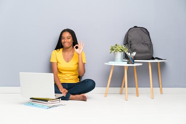 Menina adolescente estudante sentada no chão mostrando um sinal de ok com os dedos