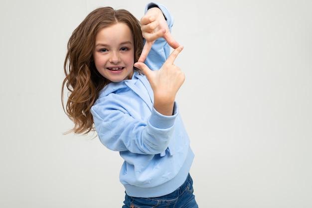 Menina adolescente europeu bonito com um capuz azul mantém os dedos na forma de um losango sobre um fundo cinza claro.