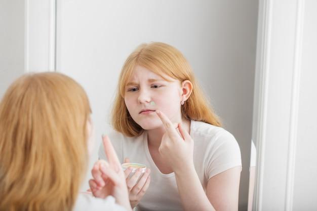 Menina adolescente examina acne na frente do espelho
