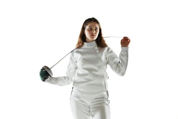 Menina adolescente fantasiada de esgrima com a espada na mão, isolada na parede branca