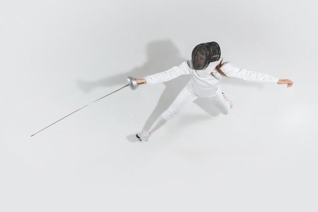 Menina adolescente fantasiada de esgrima com a espada na mão, isolada no fundo branco, vista superior