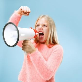Menina adolescente fazendo anúncio com megafone no estúdio azul