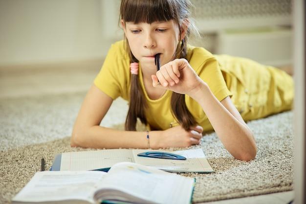 Menina adolescente, fazendo, dever casa, sentar-se tapete, em, dela, sala