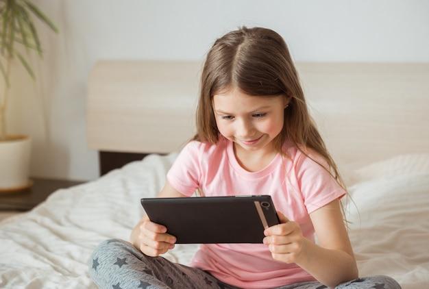 Menina adolescente feliz assistindo a um filme online com o tablet digital e deitada na cama em casa pela manhã