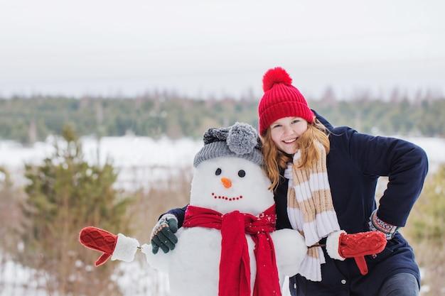 Menina adolescente feliz com boneco de neve na floresta de inverno