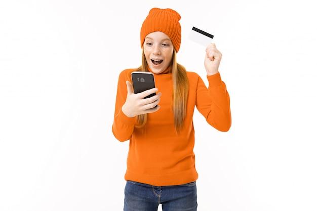Menina adolescente feliz com cabelo vermelho, casaco com capuz laranja e chapéu com cartão de crédito e telefone isolado no branco