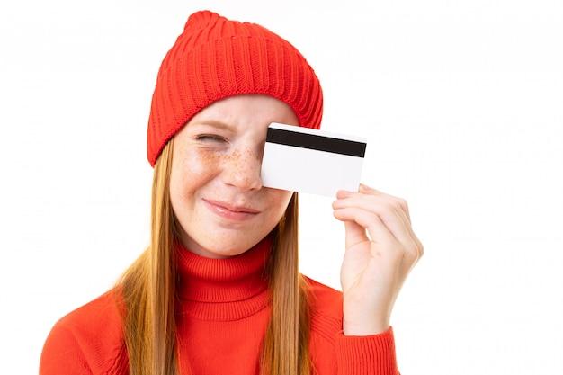 Menina adolescente feliz com cabelo vermelho, casaco com carapuço vermelho e chapéu com cartão de crédito isolado no branco