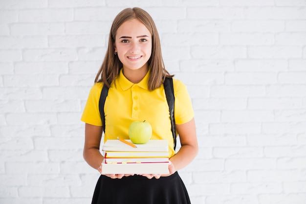 Menina adolescente feliz com livros didáticos e maçã