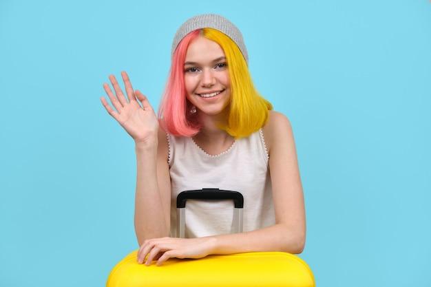 Menina adolescente feliz com mala no chapéu acena com a mão sobre fundo de cor azul. férias, olá, tchau, feriados, conceito de juventude
