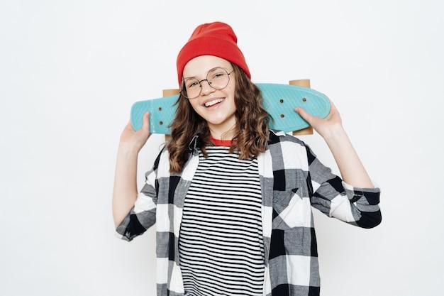 Menina adolescente feliz e elegante usando óculos, gorro vermelho, short branco e camisa xadrez, posando com uma tábua de moedas no branco