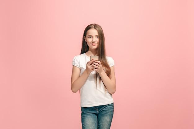 Menina adolescente feliz em pé, sorrindo com o celular em um estúdio rosa moderno