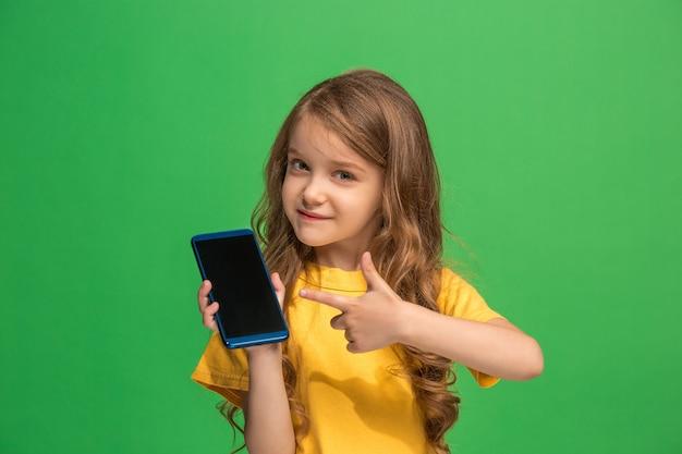 Menina adolescente feliz em pé, sorrindo com o celular na parede do moderno estúdio verde