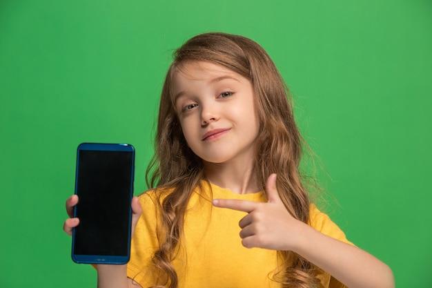 Menina adolescente feliz em pé, sorrindo com o celular sobre o fundo do estúdio verde na moda.