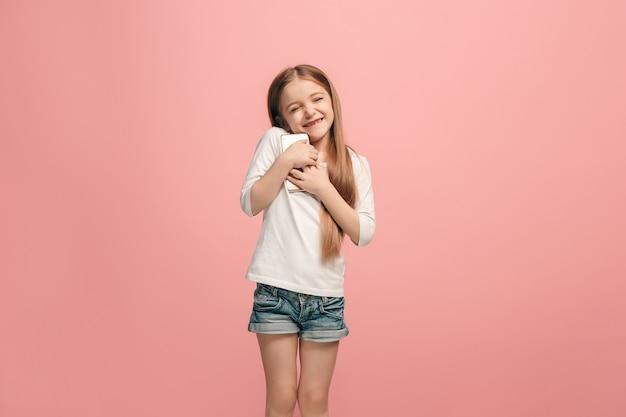 Menina adolescente feliz em pé, sorrindo com o celular sobre o fundo rosa da moda do estúdio.
