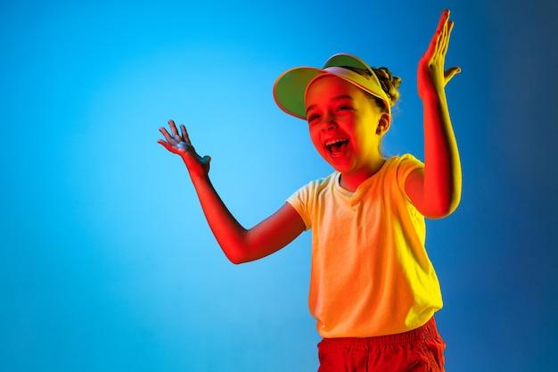 Menina adolescente feliz em pé, sorrindo e apontando para cima do moderno estúdio de néon azul