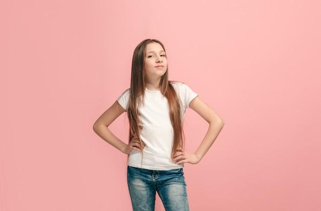 Menina adolescente feliz em pé, sorrindo, isolada na parede do estúdio rosa da moda