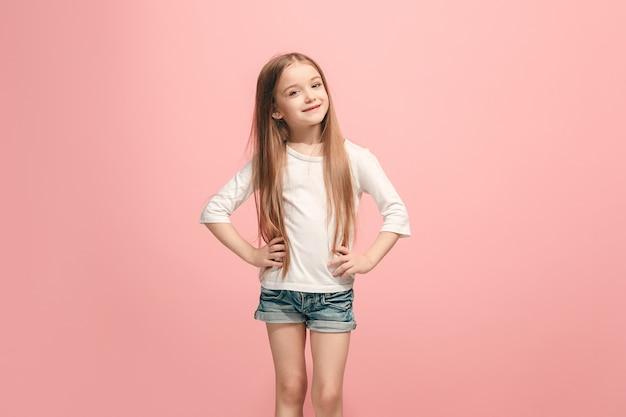 Menina adolescente feliz em pé, sorrindo, isolada no moderno estúdio rosa