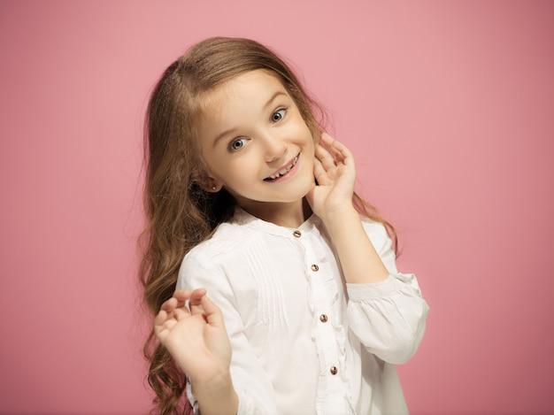 Menina adolescente feliz em pé, sorrindo isolado na parede rosa da moda. belo retrato feminino. jovem satisfazer a garota. emoções humanas, conceito de expressão facial. vista frontal.