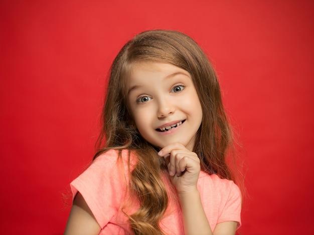 Menina adolescente feliz em pé, sorrindo isolado na parede vermelha da moda. belo retrato feminino. jovem satisfazer a garota. emoções humanas, conceito de expressão facial. vista frontal.