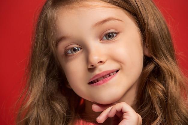 Menina adolescente feliz em pé, sorrindo isolado no estúdio vermelho da moda.