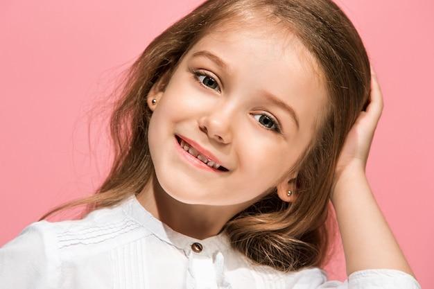 Menina adolescente feliz em pé, sorrindo isolado no fundo do estúdio rosa na moda. belo retrato feminino. jovem satisfazer garota