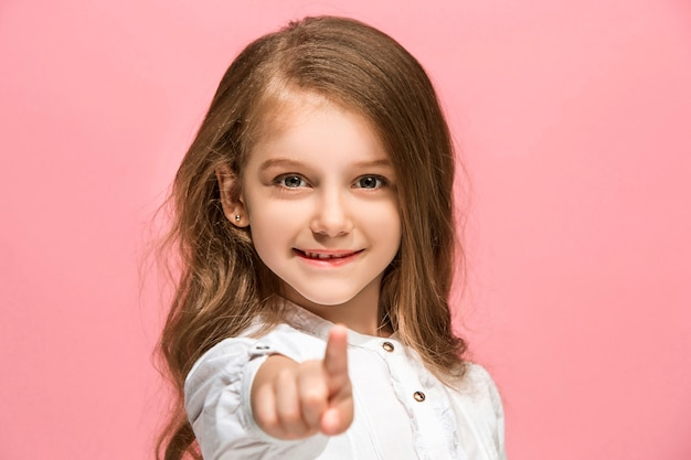 Menina adolescente feliz em pé, sorrindo isolado no fundo do estúdio rosa na moda. vista frontal.