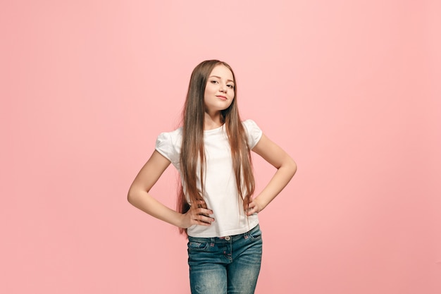Menina adolescente feliz em pé, sorrindo isolado no fundo do estúdio rosa na moda.