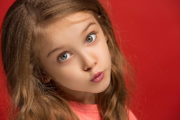 Menina adolescente feliz em pé, sorrindo isolado no fundo do estúdio vermelho da moda.
