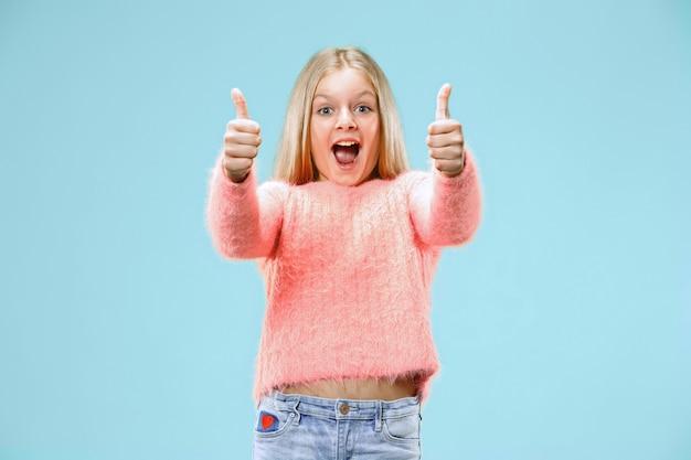 Menina adolescente feliz em pé, sorrindo isolado no moderno estúdio azul.