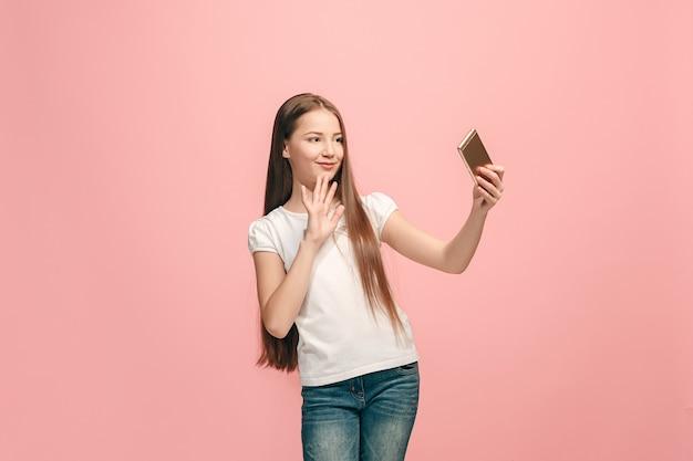Menina adolescente feliz em pé, sorrindo no fundo rosa do estúdio,