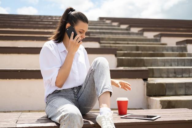 Menina adolescente feliz falando no telefone, segurando o copo de papel de café, aproveitando o dia de sol sentado no anfiteatro.
