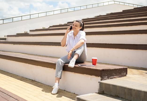 Menina adolescente feliz falando no telefone segurando um copo de papel de café, aproveitando o dia de sol sentado no anfiteatro