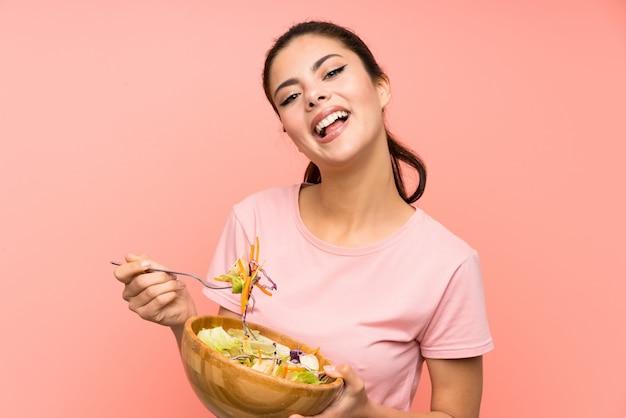 Menina adolescente feliz isolado parede rosa com salada