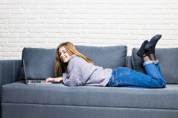 Menina adolescente feliz on-line com um laptop deitada na cama na sala de estar de casa