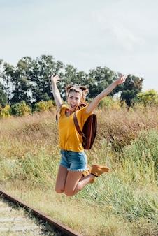 Menina adolescente feliz pulando na estrada de ferro