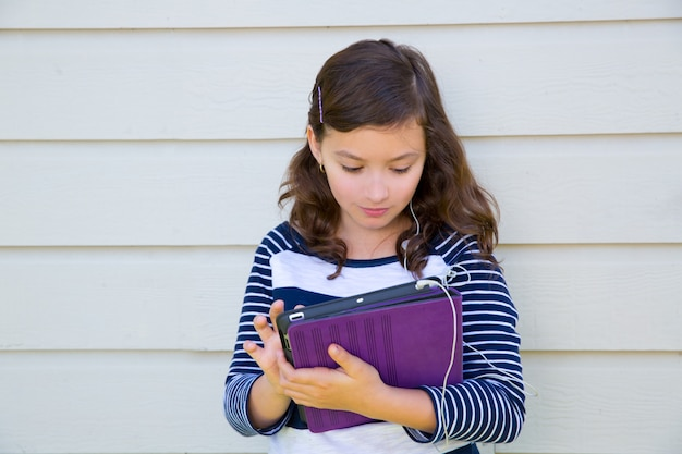 Menina adolescente feliz segurando o tablet pc e brincos