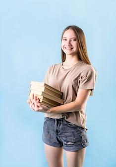 Menina adolescente feliz, segurando uma pilha de livros, isolados no fundo azul