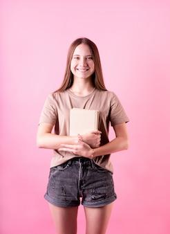 Menina adolescente feliz, segurando uma pilha de livros isolados no fundo rosa