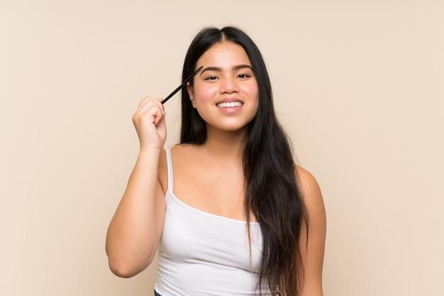 Menina adolescente feliz tomando café da manhã com uma tigela de cereais