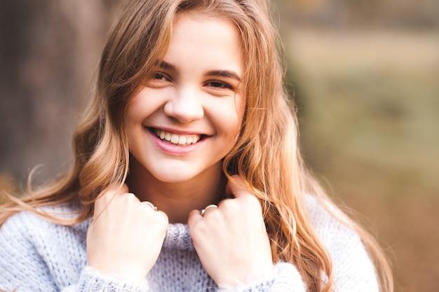 Menina adolescente feliz vestindo um suéter de tricô aconchegante ao ar livre