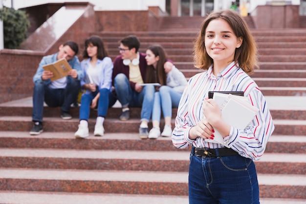 Menina adolescente, ficar, e, segurando, caderno, em, mãos