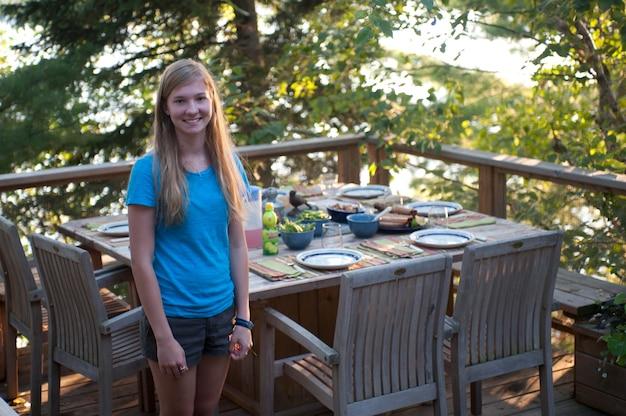 Menina adolescente, ficar, por, pátio, jantando tabela, ligado, um convés