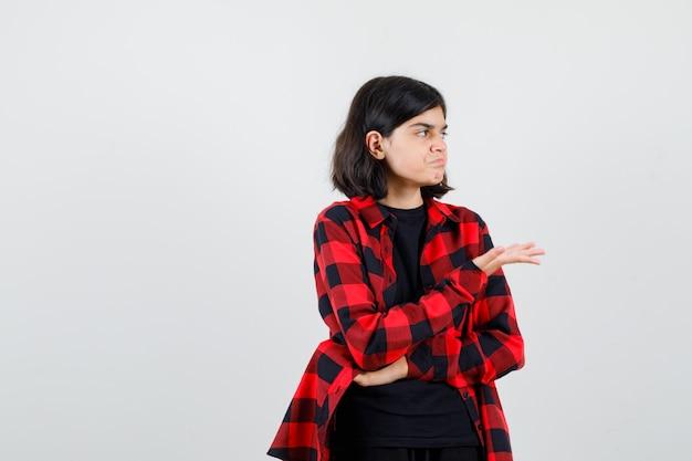 Menina adolescente fingindo mostrar algo em t-shirt, camisa quadriculada e parecendo insatisfeita, vista frontal.