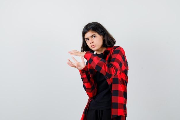 Menina adolescente fingindo segurar algo na camisa casual e olhando pensativa, vista frontal.