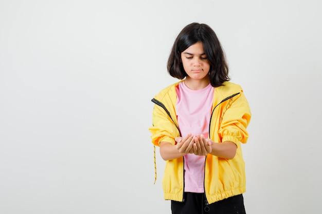 Menina adolescente fingindo segurar algo na t-shirt, jaqueta e olhando pensativa, vista frontal.
