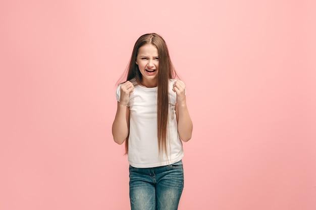 Menina adolescente furiosa parada na parede do estúdio rosa da moda