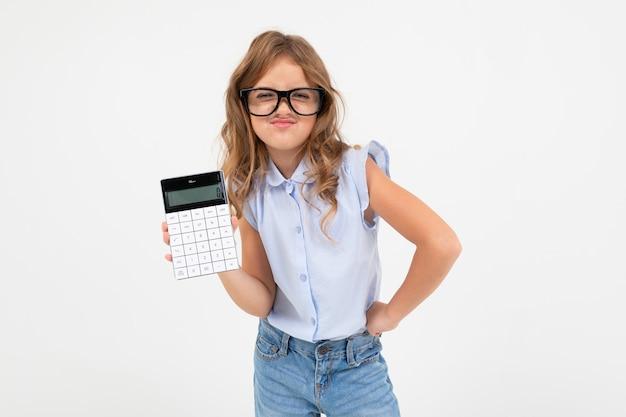 Menina adolescente inteligente, segurando uma calculadora na mão, sobre um fundo branco, com espaço de cópia