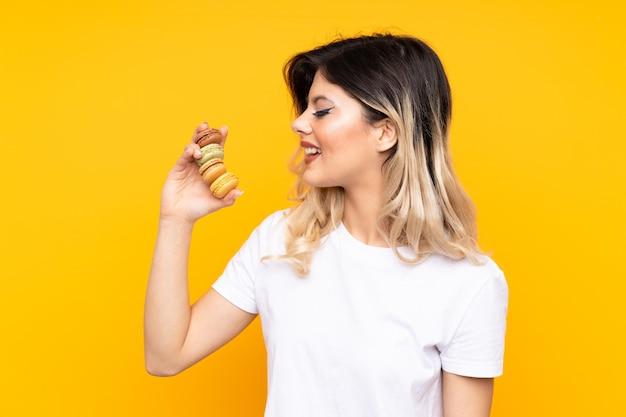 Menina adolescente isolada na parede amarela segurando macarons franceses coloridos e com uma expressão feliz