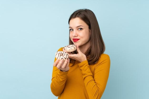 Menina adolescente isolada na parede azul, segurando um donut